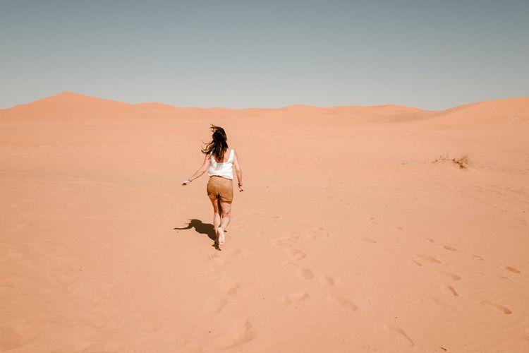 Full length of man on sand dune in desert against clear sky
