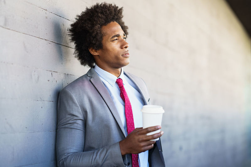 Thoughtful businessman drinking coffee while standing against wall