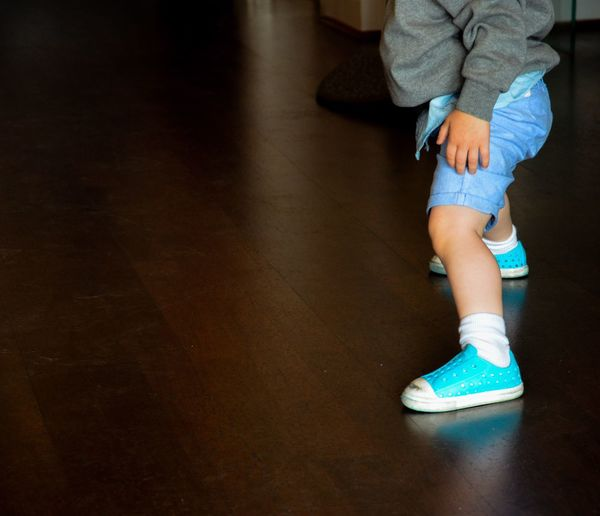 Low section of baby wearing shoes on hardwood floor