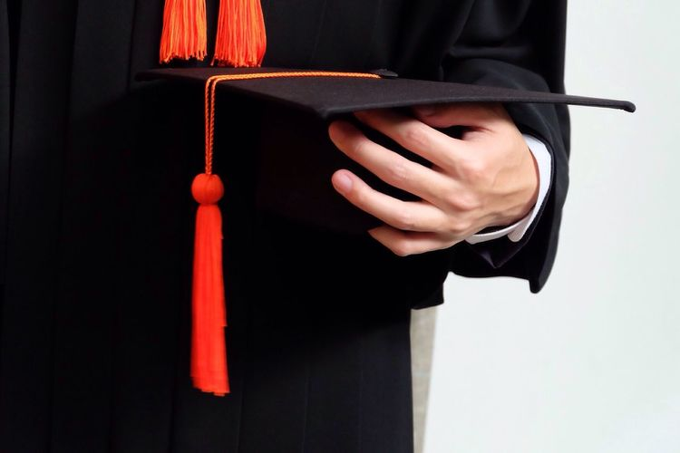 Midsection Of Man Wearing Graduation Gown While Holding Mortarboard Against White Background