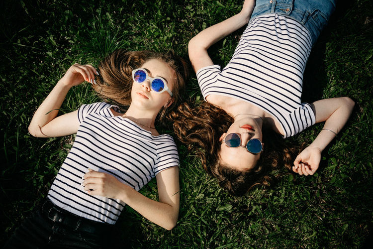 High angle view of friends lying on grass
