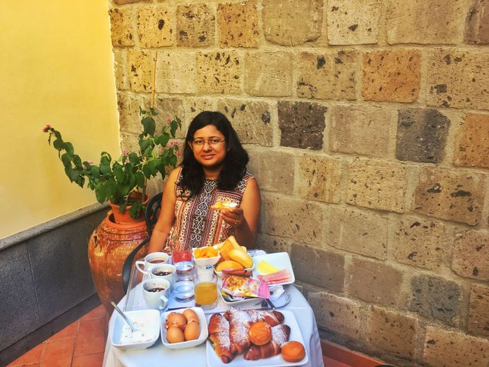 Portrait Of Woman With Breakfast Served On Table Against Wall