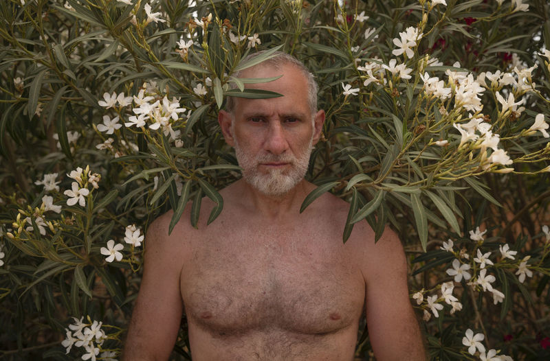 Portrait of shirtless adult man standing against plants with white flowers