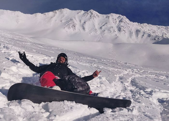 Man lying while snowboarding on snow covered mountains during winter