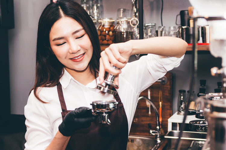 Women Barista using coffee machine for making coffee in the cafe Adult Alcohol Beautiful Woman Drink Emotion Focus On Foreground Food And Drink Front View Glass Hairstyle Happy Hour Holding Indoors  One Person Portrait Real People Refreshment Smiling Women Young Adult Young Women