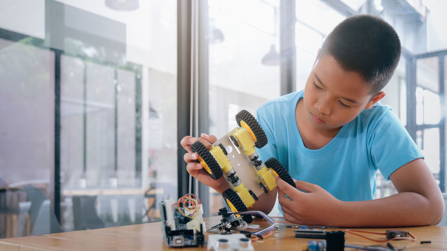 Boy repairing toy on table
