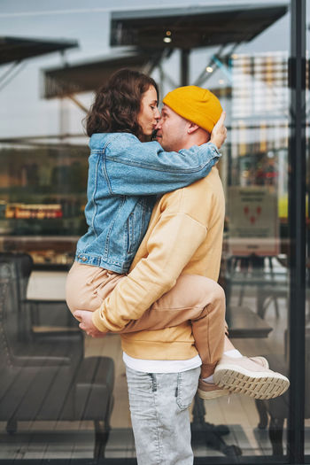 Happy stylish young family couple in love hipsters having fun against glass wall