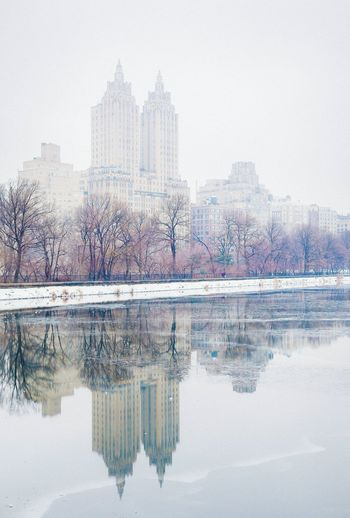 Reflection Of The Eldorado On Calm Lake In Central Park During Winter