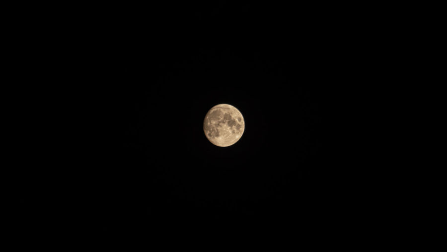 Low angle view of full moon against dark sky