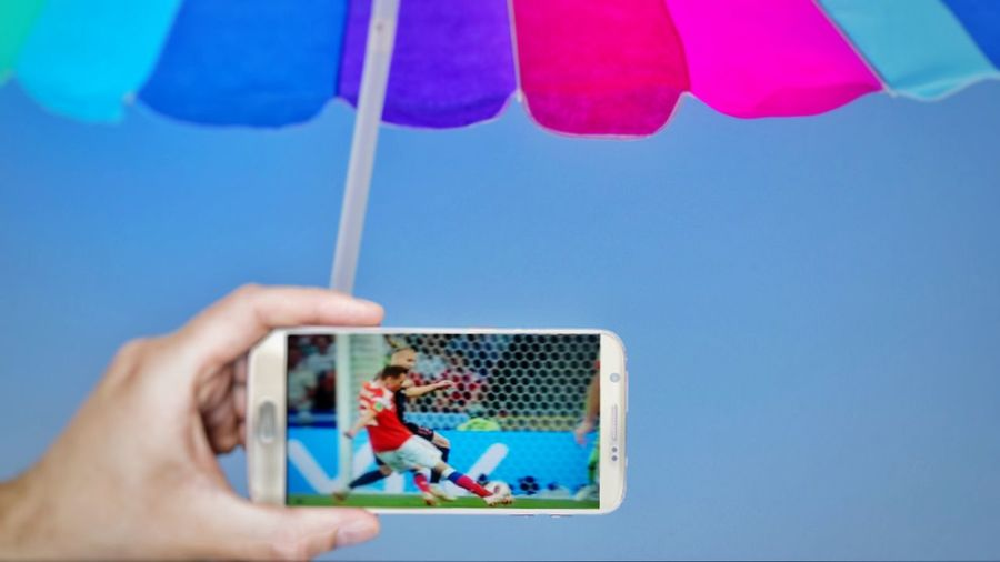 Human Body Part Human Hand Blue Day Sky Multi Colored Outdoors Clear Sky Sport Smartphone Using Mobile Tecnology Tecnology ı Can't Live Without Beach Umbrella Beach Soccer Wirless Streaming Soccer Player Soccer Fans World Cup 2018 Ondemand Love The Game