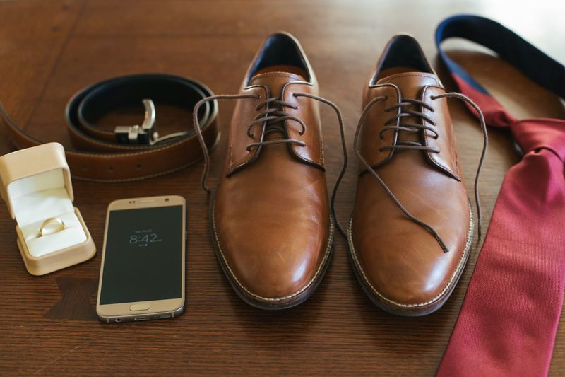 Essentials for any gentleman on wedding day Wedding Ring Box Android Phone Belt  Red Tie Shoe Still Life High Angle View Indoors  Pair Leather Table No People Brown Fashion Close-up Personal Accessory Bag Lifestyles Choice Order Group Of Objects Black Color Flat Shoe Flooring