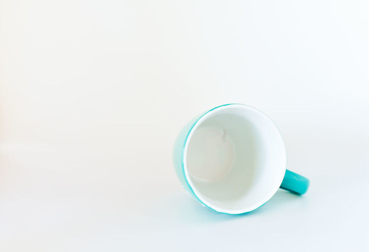High angle view of coffee cup on table against white background