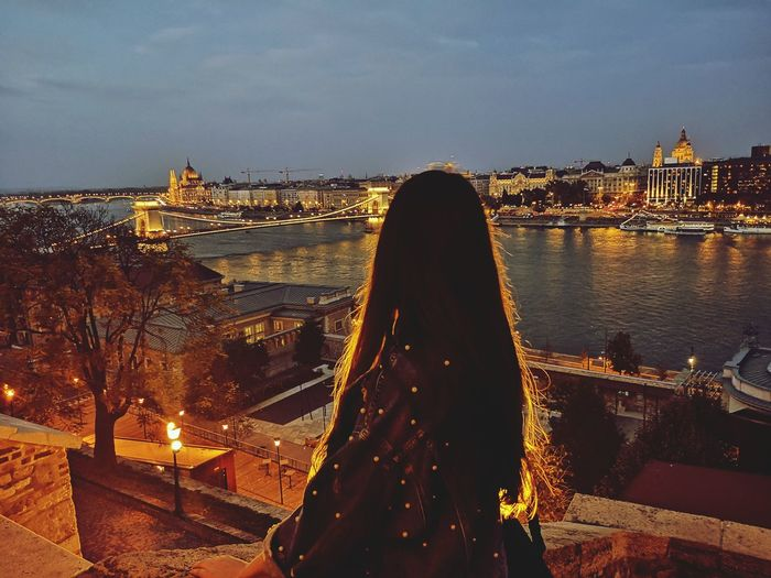 Rear view of woman standing by river against sky in city