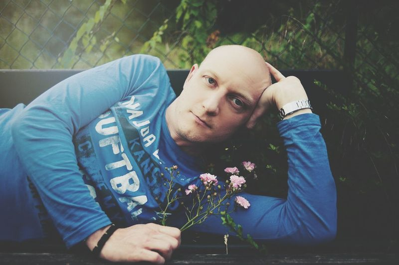 Portrait of young bald man holding flowers while reclining on bench