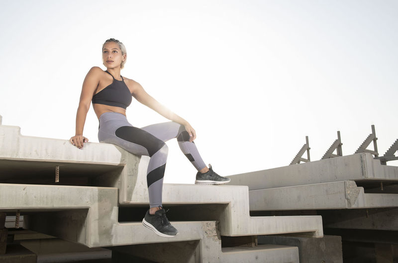 Middle Eastern Girl with short braided hair sitting on a stack of blocks on construction site wearing gray and black fitness outfit on a hot bright sunny day. Exercising Jumping Off Rocks Sitting Architecture Beautiful Woman Bright Day Clear Sky Day Dusty Exercising Fitness Model Full Length Hot Day ☀ Leisure Activity Lifestyles Looking At Camera Middle Eastern Woman Nature One Person Portrait Real People Sky Smiling Sport Sports Clothing Stretching Women Young Adult Young Women
