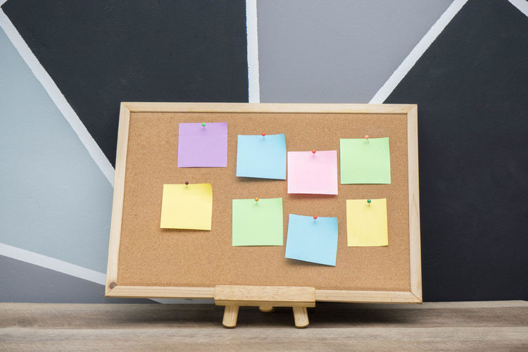 Bulletin board with colorful blank adhesive notes on table against wall