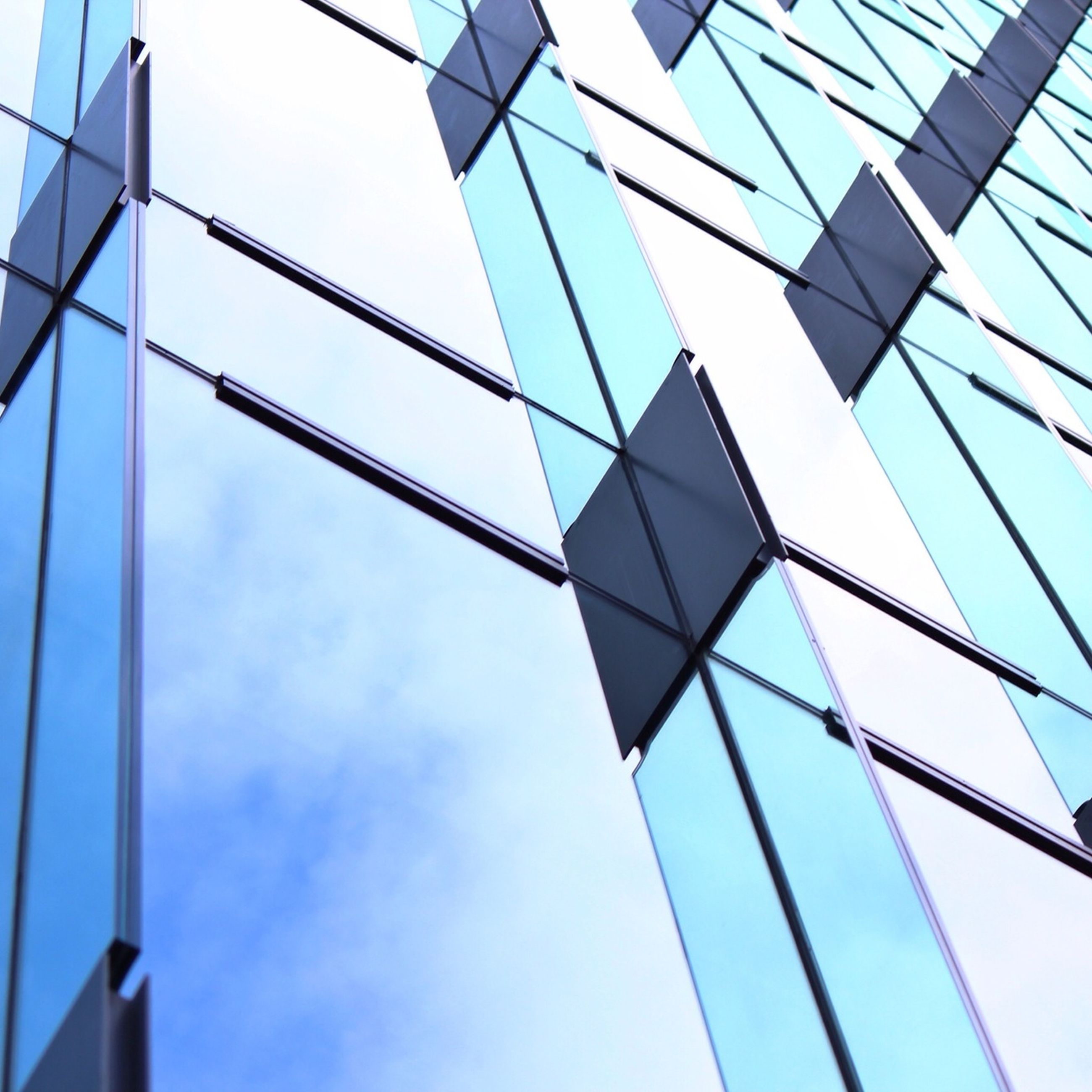 low angle view, architecture, built structure, modern, building exterior, office building, glass - material, sky, reflection, tall - high, skyscraper, building, city, tower, day, glass, cloud - sky, window, no people, directly below