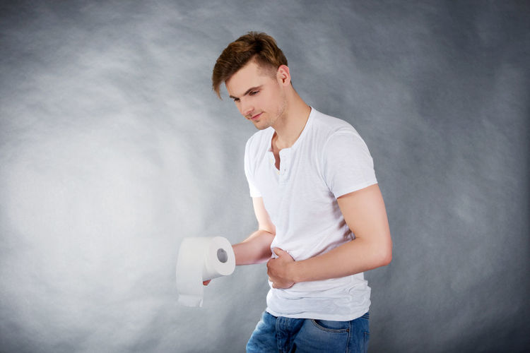 Young man holding toilet roll while standing with hand on stomach against gray backdrop