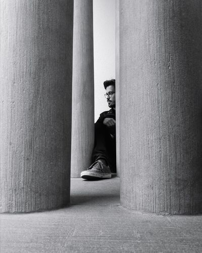 Young man sitting amidst columns