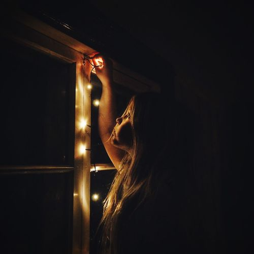 Girl decorating house window with christmas lights at night