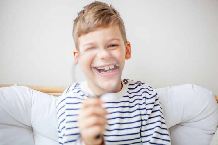 Young blond boy holding magnifying glass and smiling at camera Boys Casual Clothing Child Childhood Emotion Front View Happiness Headshot Indoors  Leisure Activity Lifestyles Males  Men One Person Portrait Real People Smiling Toothy Smile