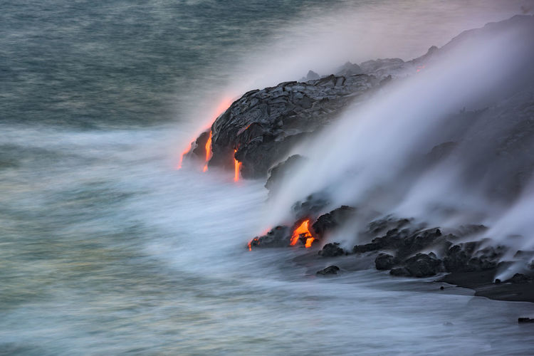 High Angle View Of Lava On Rocky Shore With Smoke At Kilauea In Hawaii