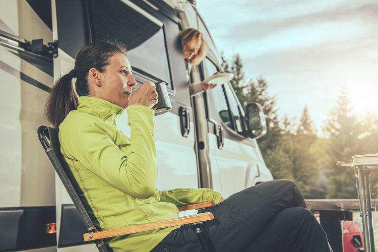 Side view of smiling woman drinking coffee while sitting by motor home