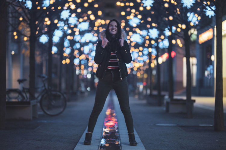 Woman standing on footpath against illuminated lights at night
