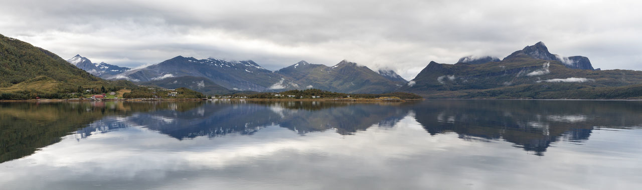 Panorama of mountain range reflecting in fjord Green Color Moody Sky Panoramic Atmospheric Mood Beauty In Nature Cloud - Sky Day Fjord Landscape Mountain Mountain Range Nature No People Nordland County Outdoors Peninsula Reflection Remote Scenics Sky Smooth Summer Symmetry Water Waterfront