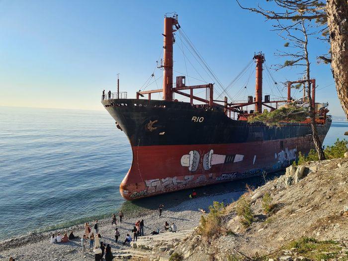 Abandoned ship on beach against clear sky