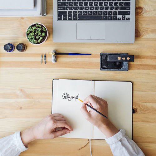 Calligraphy Calligraphyart Chinese Communication Day Desk Directly Above High Angle View Human Body Part Human Hand Indoors  Ink Laptop Laptop Keyboard Men One Person Paper People Real People Table Technology Wireless Technology Women Wristwatch