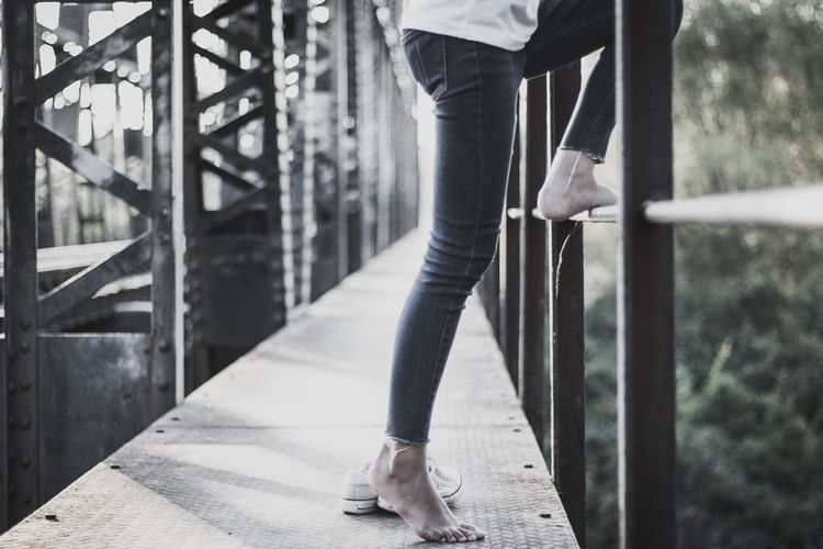 Low section of woman standing on footbridge