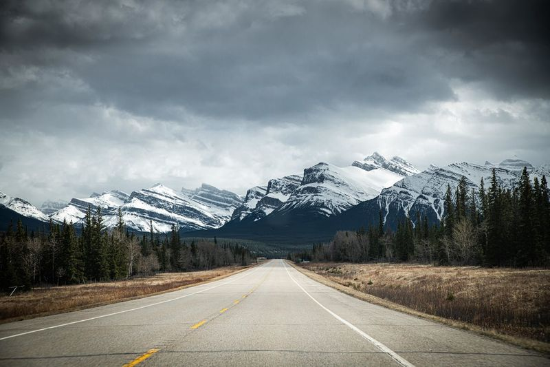 Road leading towards snowcapped mountains against cloudy sky