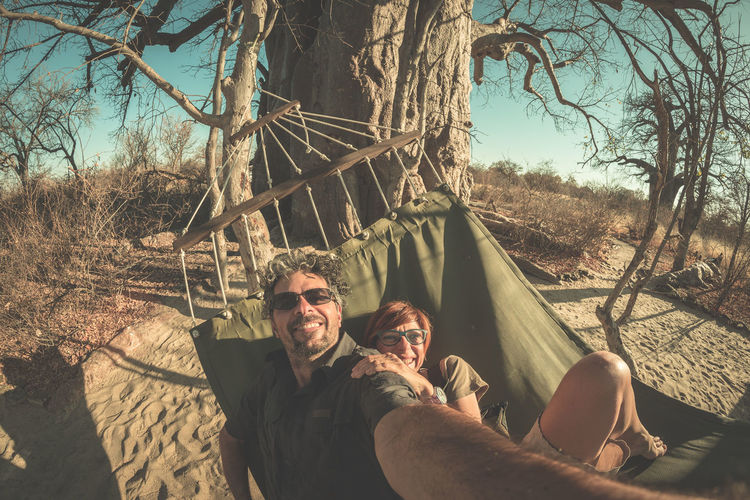 Couple taking selfie on hammock hanging from huge Baobab tree in the african savannah. Fisheye view, toned image. Wilderness safari and adventure in Africa. Bare Tree Beauty In Nature Bonding Branch Day Happiness Leisure Activity Lifestyles Looking At Camera Mature Men Nature Outdoors Photographing Photography Themes Portrait Real People Selfie Sky Smiling Togetherness Tree Two People Young Adult