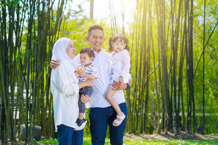Playful family spending time together at park. Group Of People Men Standing Togetherness Childhood Child Family Males  Three Quarter Length Offspring Females Boys Parent Smiling Women Happiness Mother Emotion Bonding Girls Son Daughter Innocence Positive Emotion