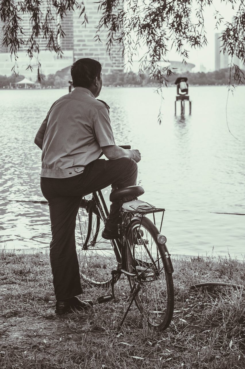 Full Length Of Man With Bicycle On Riverbank