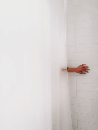 Cropped Hand Against Tiled Wall In Bathroom