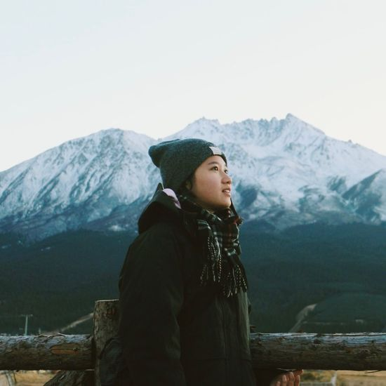Full length of woman standing on snowcapped mountain against sky