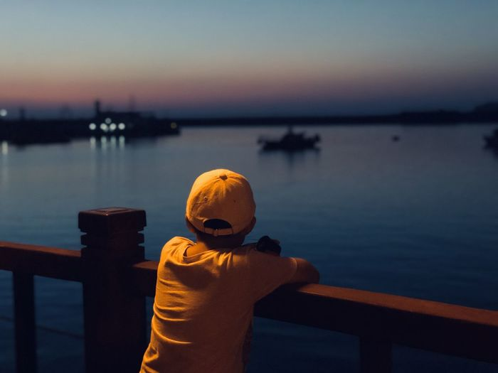 Rear view of boy standing by railing against sky during sunset