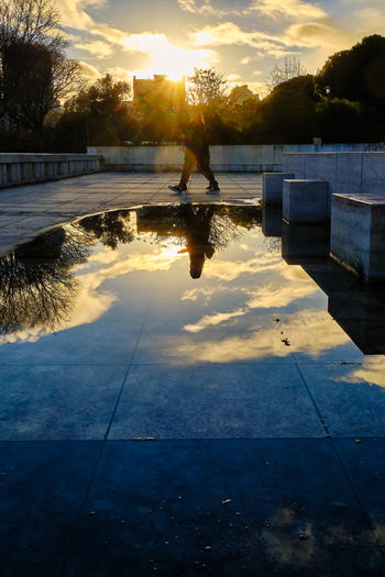 Silhouette woman by swimming pool against sky during sunset