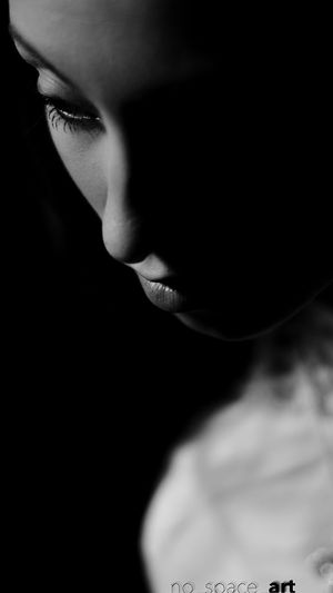 High section of young woman against black background