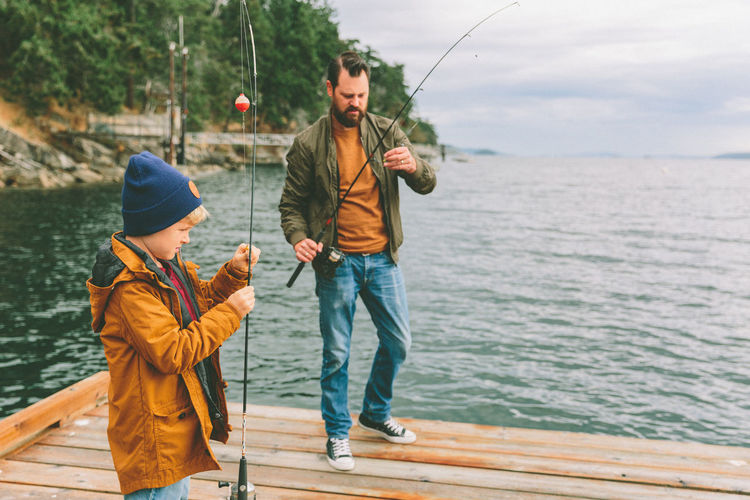 Father And Son Holding Fishing Rods While Standing By Sea