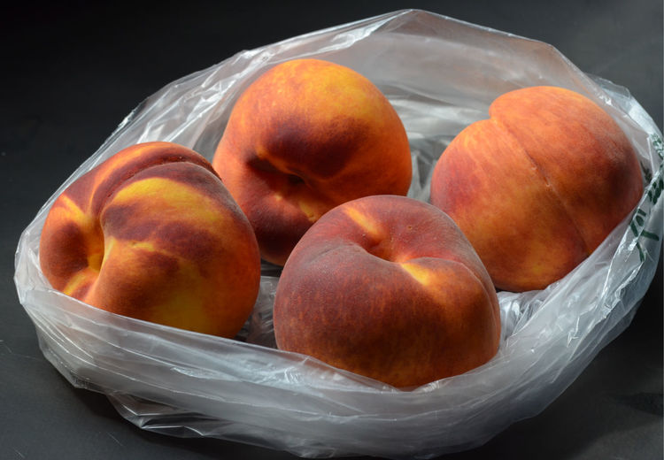 Four peaches in plastic grocery store bag