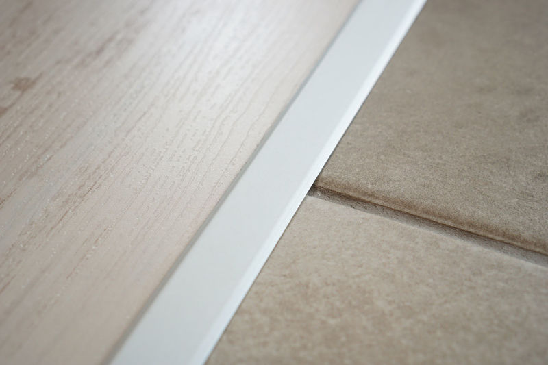 Laminate and tile transition with aluminium profile Laminate Flooring Close-up Laminate Laminate And Tile Tiled Floor