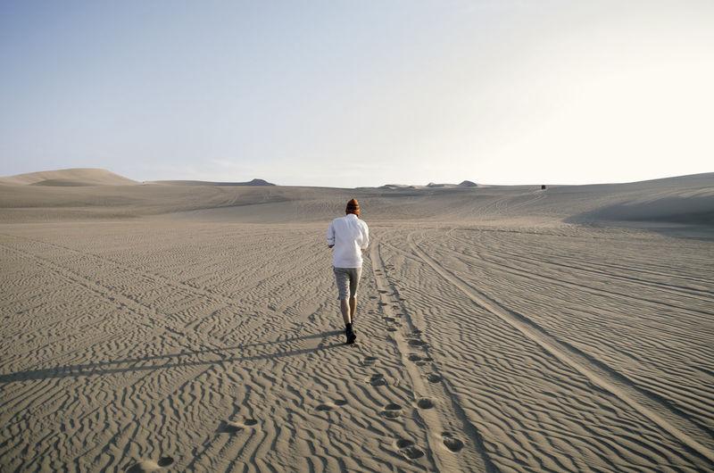 Rear View Of Man Walking On Sand At Desert