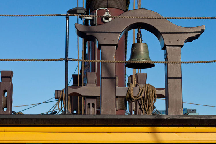 Low Angle View Of Bell On Ship Against Clear Blue Sky