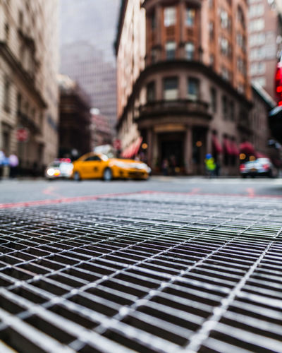 Surface level of metal grate on gutter by road in city