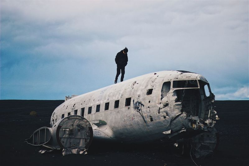 Man Standing On Solheimasandur Plane Wreck At Black Sand Beach Against Sky