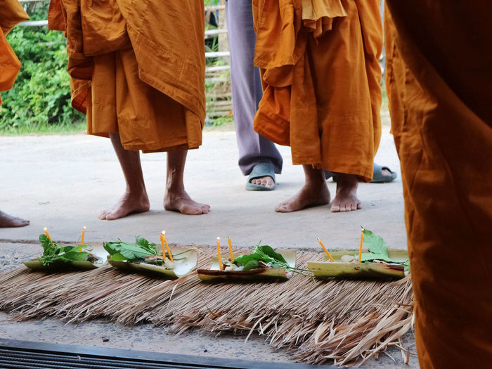 Low section of monks standing by religious offerings on walkway