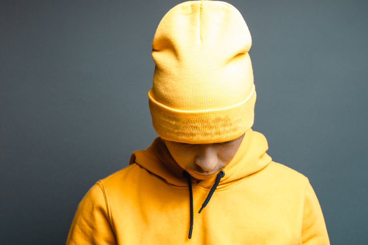 portrait of young rapper with yellow beanie cap and hoodie looking down in front of grey background Studio Shot Headshot Beanie Cap Beanie Hip-Hop Rapper Indoors  Yellow Gray Background Clothing Style Hoodie Hood - Clothing Looking Down Upset Lifestyle Teen Old School Isolated Cool